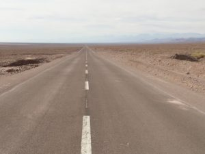 Lange leere Straße in der Atacama, Wüste in Chile - ein weiter Weg