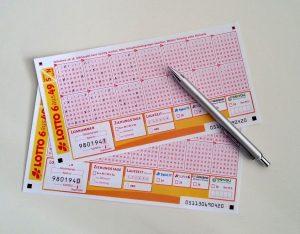 zwei Lottoscheine mit silbernem Kugelschreiber